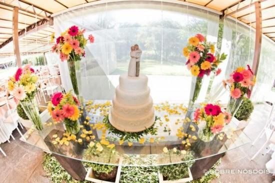 Mesa do bolo em casamento no campo: gérberas amarelas, pink e rosas. Foto: Sobre Nós Dois.