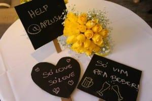 Plaquinhas de lousa com mensagem para casamento e buquê de tulipas amarelas.