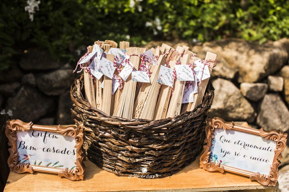 Casamento ao ar livre: chapéus de palha e leques de madeira são ideias de mimos para os convidados. Foto: Juan Cogo Fotografia.
